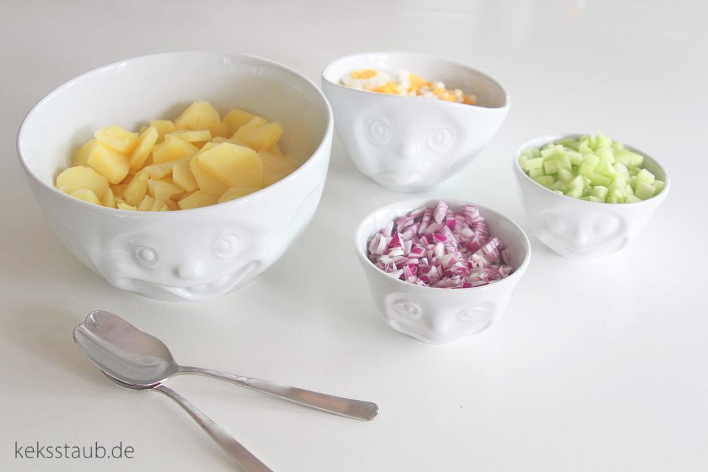 Kartoffelsalat geschnittene Zutaten Gurke rote Zwiebeln Kartoffeln Eier logo